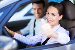 Coppie che si siedono in automobile con i pollici su Immagini Stock Libere da Diritti