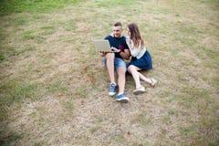 Coppie che si siedono con il computer portatile sull'erba Fotografia Stock