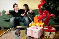 Coppie che si siedono davanti all'albero di Natale Fotografia Stock
