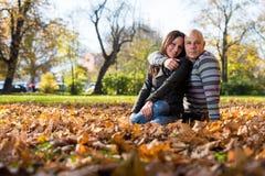 Coppie che si siedono insieme nel legno durante l'autunno Fotografia Stock