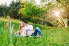 Coppie che si siedono insieme sull'erba fotografia stock