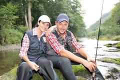 Coppie che si siedono nel fiume con le righe di pesca Immagini Stock