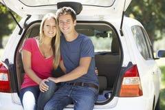 Coppie che si siedono nel tronco dell'automobile Fotografia Stock