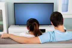 Coppie che si siedono su Sofa In Front Of Television Fotografie Stock Libere da Diritti