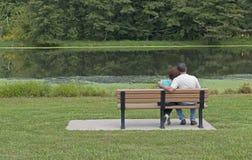 Coppie che si siedono su un banco in primavera fotografia stock