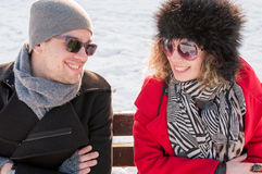 Coppie che si siedono sul banco nell'inverno Immagine Stock