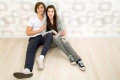 Coppie che si siedono sul pavimento Fotografia Stock