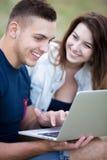 Coppie che si siedono sul prato inglese con il computer portatile Fotografia Stock Libera da Diritti
