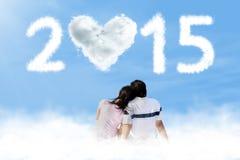 Coppie che si siedono sulla nuvola con il numero 2015 Immagine Stock Libera da Diritti