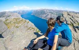 Coppie che si siedono sulla roccia che gode della vista del fiordo, vicino a Preikestolen, la Norvegia fotografia stock