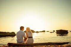 Coppie che si siedono sulla spiaggia all'alba Immagini Stock