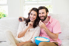 Coppie che si siedono sulla televisione di sorveglianza del sofà Fotografie Stock