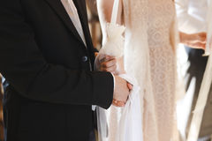 Coppie che si tengono per mano durante la cerimonia di nozze in chiesa Immagine Stock