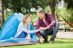 Coppie che si tengono per mano mentre installando tenda in parco fotografia stock libera da diritti