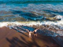 Coppie che si tengono per mano sull'antenna della spiaggia fotografie stock