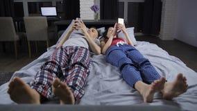 Coppie che si trovano a letto con i telefoni cellulari in mani video d archivio