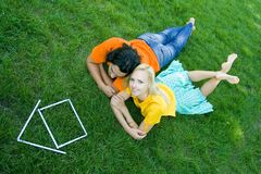 Coppie che si trovano sull'erba con la casa di modello Immagine Stock