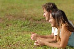 Coppie che si trovano sull'erba e sul distogliere lo sguardo Fotografia Stock Libera da Diritti