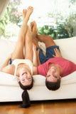 Coppie che si trovano upside-down sul sofà Immagini Stock Libere da Diritti