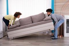 Coppie che sollevano Sofa In Living Room fotografia stock libera da diritti
