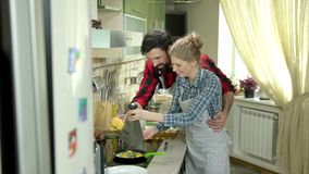 Coppie che sorridono e che cucinano alimento stock footage