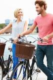 Coppie che spingono le bici con l'orizzonte della città nel fondo Fotografia Stock Libera da Diritti