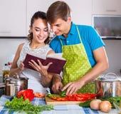 Coppie che stanno con il libro di cucina in cucina Fotografie Stock Libere da Diritti