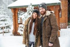 Coppie che stanno vicino al cottage di legno nell'inverno Immagine Stock Libera da Diritti