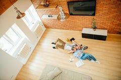 Coppie che studiano mentre trovandosi sul pavimento a casa Immagini Stock