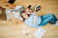 Coppie che studiano mentre trovandosi sul pavimento a casa Immagine Stock Libera da Diritti