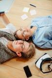 Coppie che studiano mentre trovandosi sul pavimento a casa Fotografie Stock