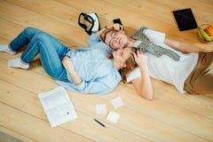 Coppie che studiano mentre trovandosi sul pavimento a casa Immagine Stock