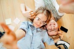 Coppie che studiano mentre trovandosi sul pavimento a casa Immagini Stock Libere da Diritti