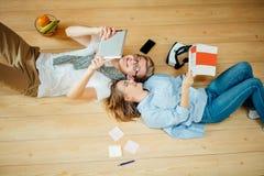 Coppie che studiano mentre trovandosi sul pavimento a casa Fotografia Stock Libera da Diritti
