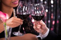 Coppie che tostano i bicchieri di vino in ristorante Fotografia Stock Libera da Diritti