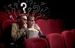 Coppie in cinema con le domande fotografia stock