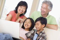 Coppie con due bambini nella sala con il computer portatile fotografia stock