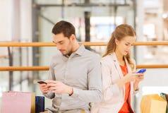 Coppie con gli smartphones ed i sacchetti della spesa in centro commerciale Fotografia Stock Libera da Diritti
