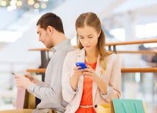 Coppie con gli smartphones ed i sacchetti della spesa in centro commerciale Immagine Stock Libera da Diritti