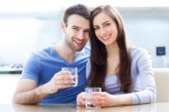 Coppie con i bicchieri d'acqua Fotografia Stock