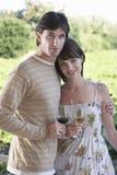 Coppie con i bicchieri di vino al campo Immagini Stock