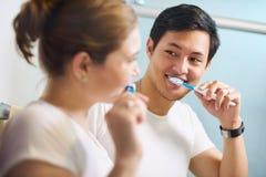 Coppie con i denti di lavaggio dell'uomo e della donna dello spazzolino da denti insieme Immagini Stock