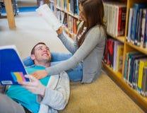 Coppie con i libri alla navata laterale delle biblioteche Fotografia Stock Libera da Diritti