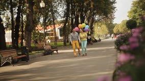 Coppie con i palloni che camminano tramite i vicoli del parco archivi video
