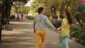 Coppie con i palloni con i sorrisi che camminano nel parco stock footage