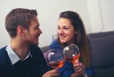 Coppie con i vetri del tintinnio del vino rosso i loro vetri i Fotografia Stock