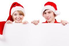 Coppie con il bordo vuoto in bianco dell'insegna Natale Fotografie Stock Libere da Diritti