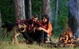 Coppie con il cane da pastore tedesco vicino al falò, fotografie stock libere da diritti