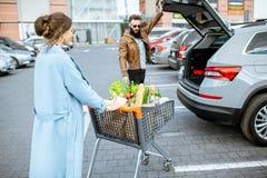 Coppie con il carrello in pieno di alimento sul parcheggio all'aperto fotografia stock