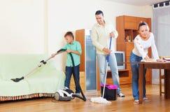 Coppie con il figlio adolescente che fa pulizia della casa Immagini Stock